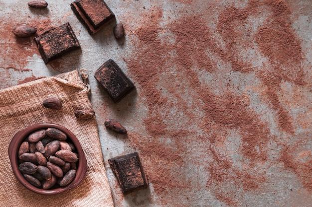 Zerstreutes kakaopulver mit schokoladenstücken und kakaobohnenschüssel