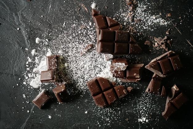 Zertrümmerte nachtischschokolade mit puderzucker auf schiefer