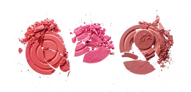 Zertrümmerte rosa errötende kosmetik lokalisiert auf weiß