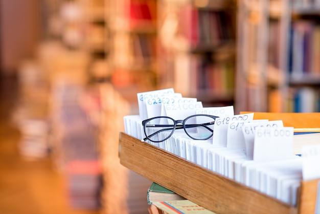 Zettelkatalog mit brille in der bibliothek. bild mit textfreiraum