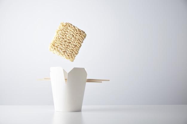 Ziegel aus trockenen nudeln fällt in eine leere imbissschachtel mit essstäbchen, die auf einem weißen kommerziellen einzelhandelsset isoliert sind