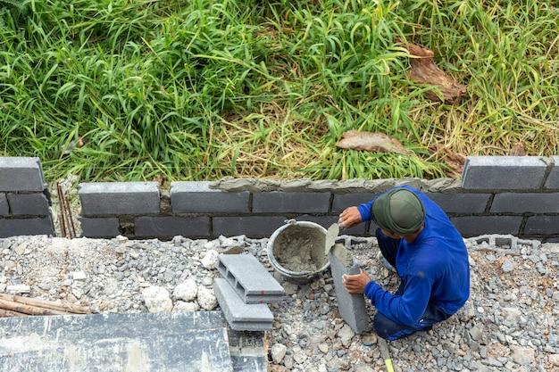Ziegelmauerzaun für ein sicheres zuhause mit arbeitskraft und zement herstellen