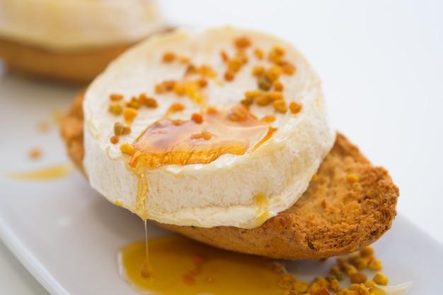 Ziegenkäse mit honig und blütenstaub auf weißer platte
