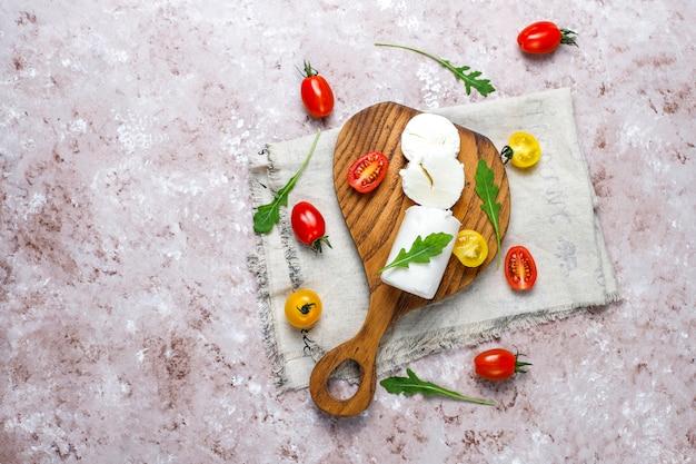 Ziegenkäse-scheiben auf hölzernem brett mit ruccola, kirschtomaten. fertig für den verzehr.