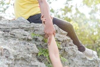 Ziehen Sie die Hand um Hilfe von der Klippe