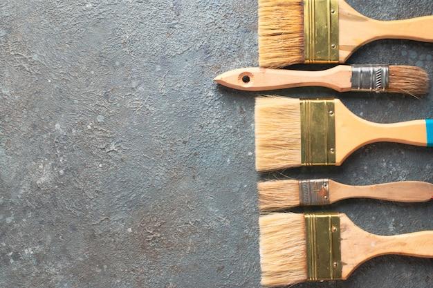 Ziehwerkzeugmalerpinsel auf grauem zementhintergrund, draufsicht