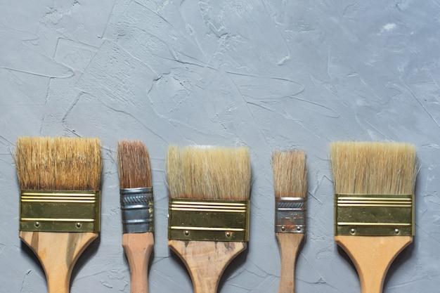 Ziehwerkzeugmalerpinsel auf grauer zementtabelle, draufsicht