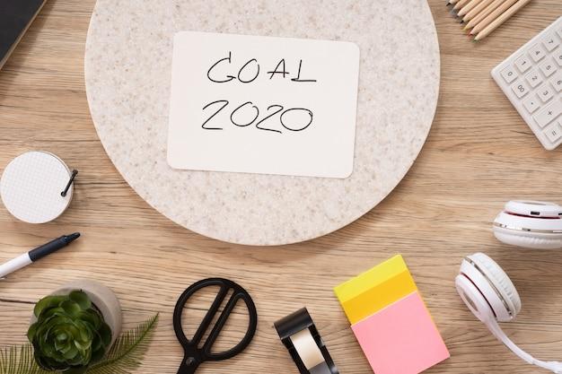 Ziel 2020 des neuen jahres auf draufsicht des papiers am hölzernen bürotisch mit briefpapiermaterial. geschäftsvision.