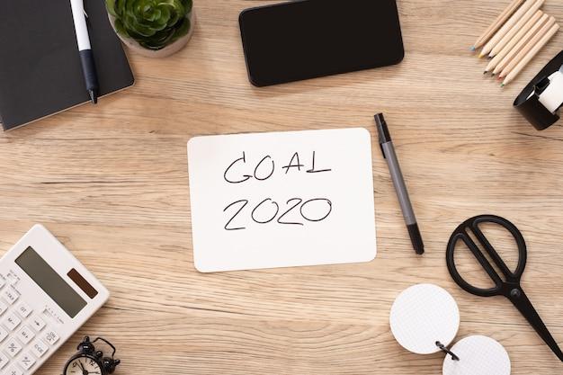 Ziel 2020 des neuen jahres auf draufsicht des papiers am hölzernen bürotisch mit briefpapiermaterial