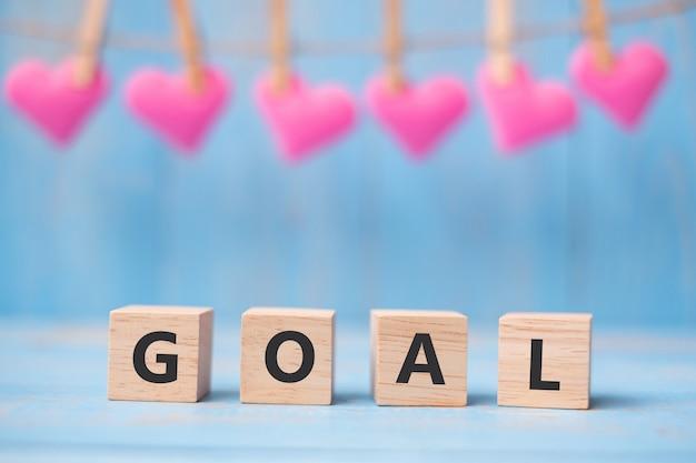 Ziel hölzerne würfel mit rosa herzform decorationon auf blauem tabellenhintergrund mit kopienraum für text. business, mission, core value, solution und happy valentine's ferienkonzept