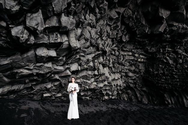 Ziel island hochzeit die braut in einem weißen seidenkleid mit einem blumenstrauß in den händen steht auf