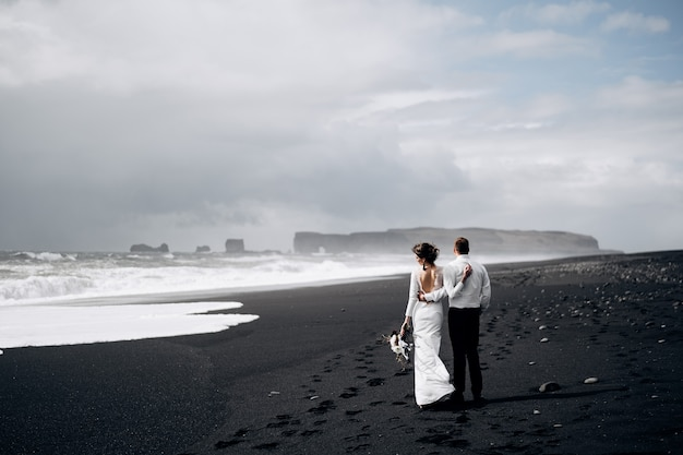 Ziel island hochzeit ein hochzeitspaar geht am schwarzen strand von vic sandstrand entlang Premium Fotos