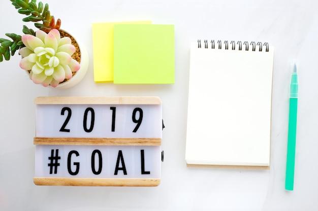 Ziele 2019 auf hölzernem kasten und leerem notizbuchpapier auf weißem marmorhintergrund