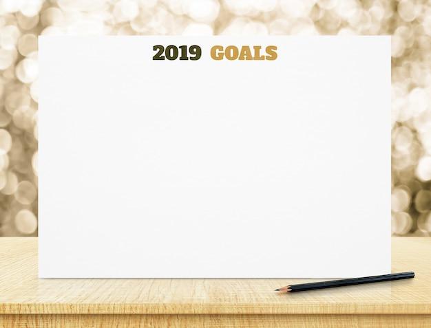 Ziele 2019 auf weißbuchplakat auf hölzerner tabelle mit goldbokeh beleuchtet am hintergrund