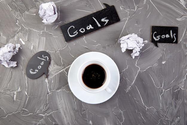 Ziele als notiz auf notizbuch mit idee, zerknittertem papier, tasse kaffee