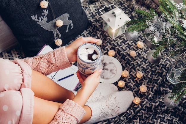 Ziele für das nächste jahr mit einer tasse schokolade unter dem weihnachtsbaum festhalten