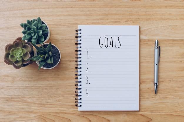 Ziele liste. schreibtisch tisch mit notizbüchern und bleistift mit topfpflanze.