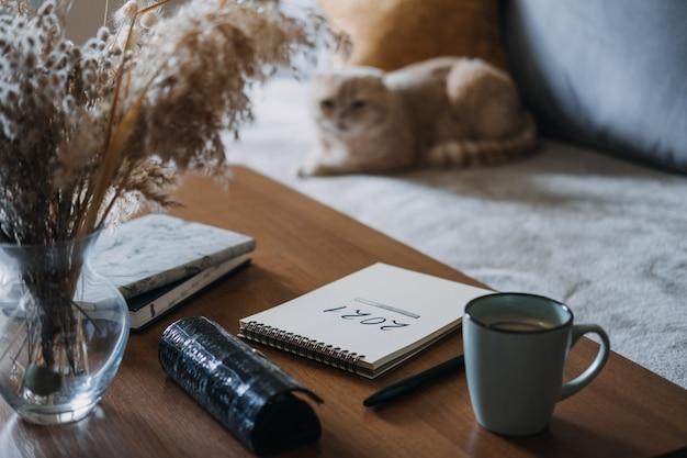 Ziele neujahrsauflösungsplanungsnotizbuch mit textladen auf dem tisch in wohnungen mit katze