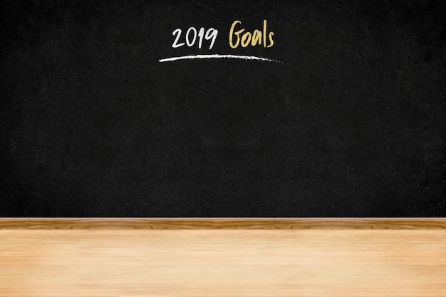 Zielschrifthandschrift 2019 auf tafelwand auf hölzernem plankenboden, geschäft presentati des neuen jahres