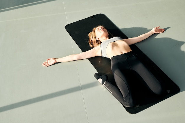 Ziemlich aktives mädchen im trainingsanzug, das auf einer schwarzen matte mit ausgestreckten armen und in knien gebeugten beinen liegt, während entspannungsübung übt