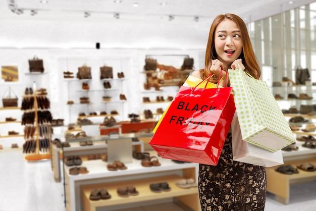 Ziemlich asiatische frau mit farbigen einkaufstüten