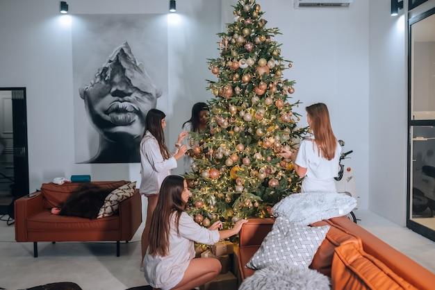 Ziemlich attraktive frauen schmücken den weihnachtsbaum mit bällen