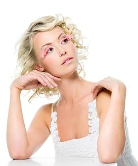 Ziemlich attraktive schönheitsfrau mit glamour-make-up. blond mit rosa wimpern