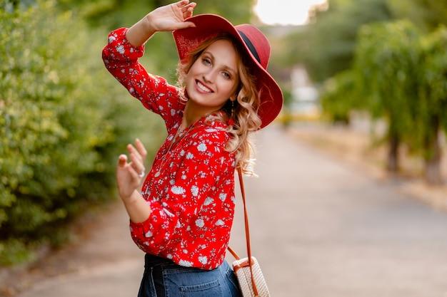 Ziemlich attraktive stilvolle blonde lächelnde frau in strohrotem hut und bluse sommermode-outfit
