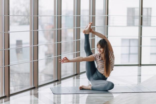 Ziemlich attraktives mädchen, das yoga in einem hellen raum tut