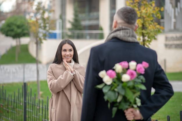 Ziemlich aufgeregte frau, die ihren freund ansieht, während sie auf ein geschenk von ihm wartet