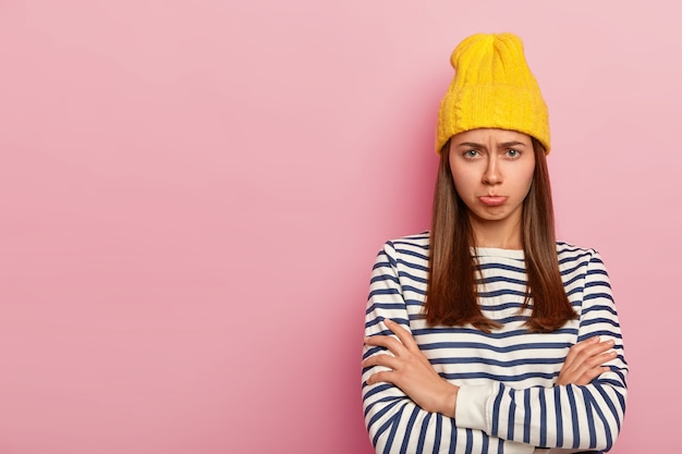 Ziemlich beleidigte frau sieht mit traurigem ausdruck aus, runzelt die stirn und spitzt die lippen vor missfallen, hält die arme verschränkt, trägt einen eleganten gelben hut und einen gestreiften pullover, modelle über der rosa wand, leeren raum