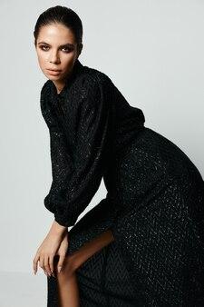 Ziemlich brünette attraktive look schwarze kleider posieren modell.