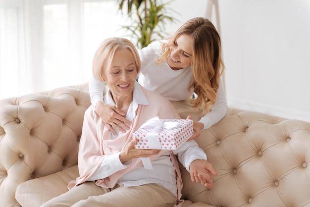 Ziemlich charmante ältere frau, die auf der couch sitzt und eine geschenkbox von ihrer erwachsenen tochter erhält, die sie mit einer hand umarmt