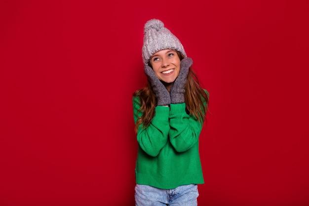 Ziemlich charmante junge frau an der roten wand im winteroutfit