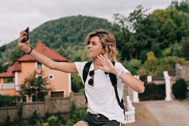 Ziemlich charmante reisende frau, die selfie auf smartphone über berg in sonnigem guten tag macht. reisekonzept, urlaub, reise