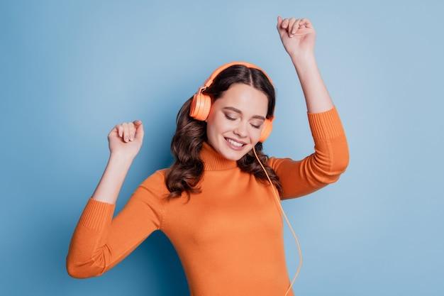 Ziemlich cooles lächelndes mädchen, das musik in kopfhörern verträumter tanz über blauem hintergrund hört