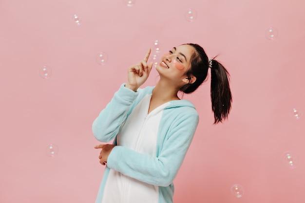 Ziemlich cooles mädchen in blauem kigurumi lächelt, spielt mit blasen und posiert mit kosmetischen augenklappen auf rosa isolierter wand