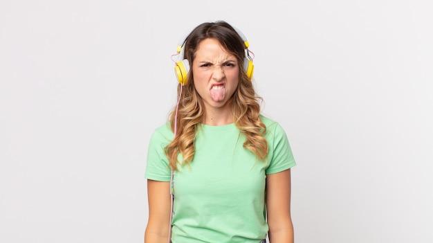 Ziemlich dünne frau, die sich angewidert und gereizt fühlt und die zunge herausstreckt, wenn sie musik mit kopfhörern hört