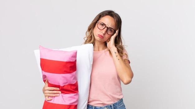 Ziemlich dünne frau, die sich gelangweilt, frustriert und schläfrig fühlt, nachdem sie einen ermüdenden schlafanzug trägt und ein kissen hält