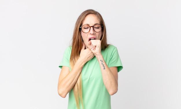 Ziemlich dünne frau, die sich mit halsschmerzen und grippesymptomen krank fühlt und mit bedecktem mund hustet