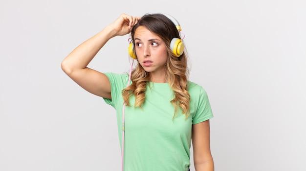 Ziemlich dünne frau, die sich verwirrt und verwirrt fühlt, sich am kopf kratzt und musik mit kopfhörern hört