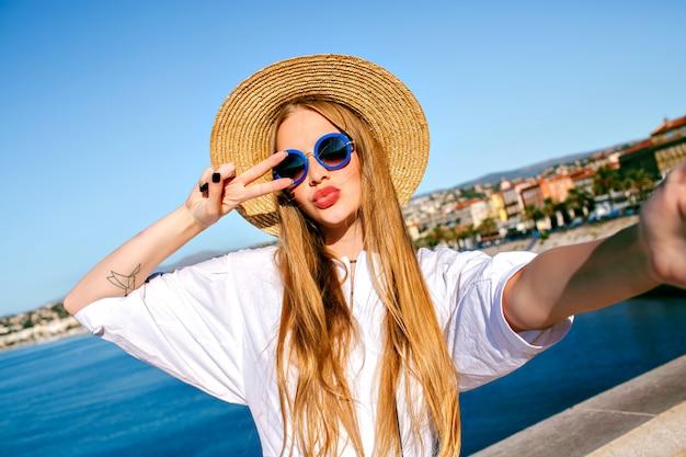 Ziemlich elegante blonde schöne frau, die selfie vorne am schönen strand macht