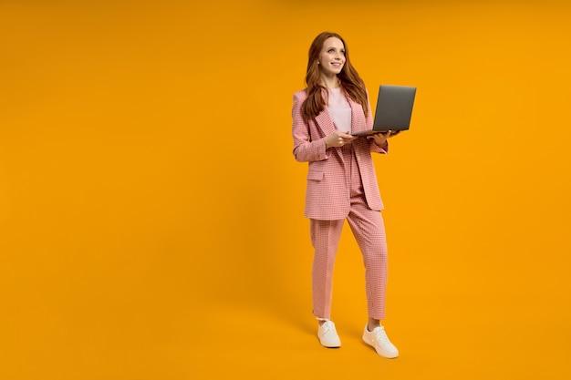Ziemlich elegante, foxy ingwer rothaarige dame, die einen laptop trägt, isoliert auf leuchtend gelb-orangeem studiohintergrund, kopierraum. kaukasische frau, die am laptop arbeitet, freiberuflich