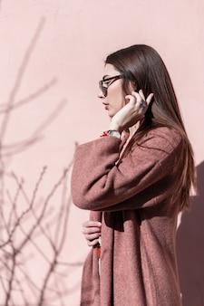 Ziemlich elegantes modemodell der jungen frau mit wunderschönen langen haaren in modischem mantel in trendiger sonnenbrille, die an einem sonnigen tag in der nähe der rosafarbenen wand posiert. stilvolles mädchen im frühjahr trägt in der sonne posiert.