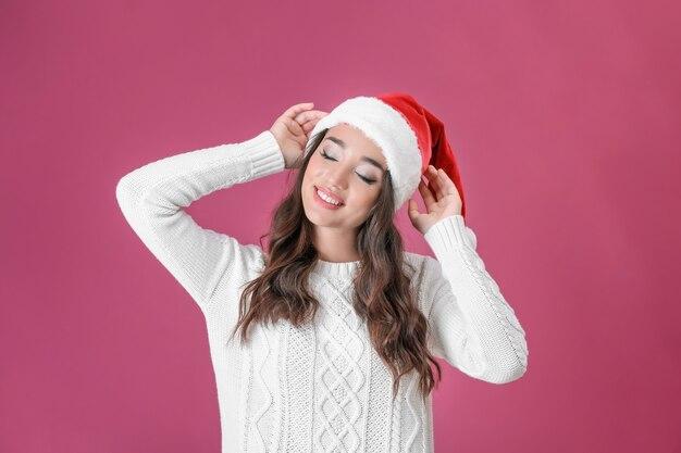 Ziemlich emotionale dame mit weihnachtsmütze auf farbfläche