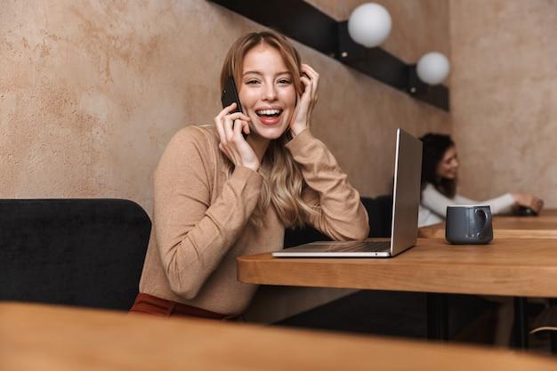 Ziemlich emotionales glückliches mädchen, das im café sitzt und mit dem handy spricht