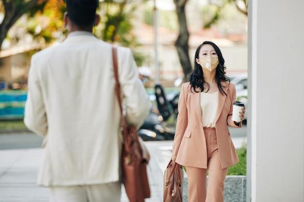 Ziemlich ernsthafte junge asiatische geschäftsfrau in schutzmaske, die am morgen mit herausgenommenem kaffee in den händen zur arbeit geht