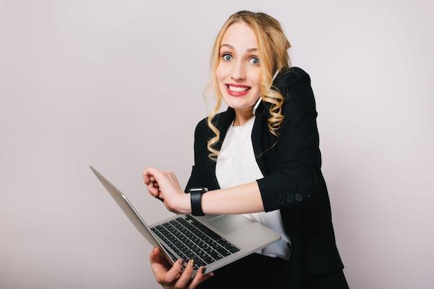 Ziemlich freudige blonde geschäftsfrau mit laptop, der am telefon lokalisiert spricht. tragen eines büroanzugs, stilvoll, modisch, beschäftigt, lächelnd, wahre emotionen