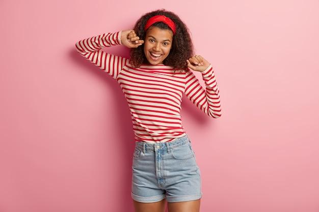 Ziemlich freudiges junges mädchen mit dem lockigen haar, das im gestreiften roten pullover aufwirft