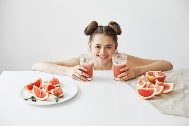 Ziemlich fröhliche frau mit brötchen lächelnd am tisch sitzen mit scheiben grapefruit gesunde detox-diät smoothie über weiße wand.